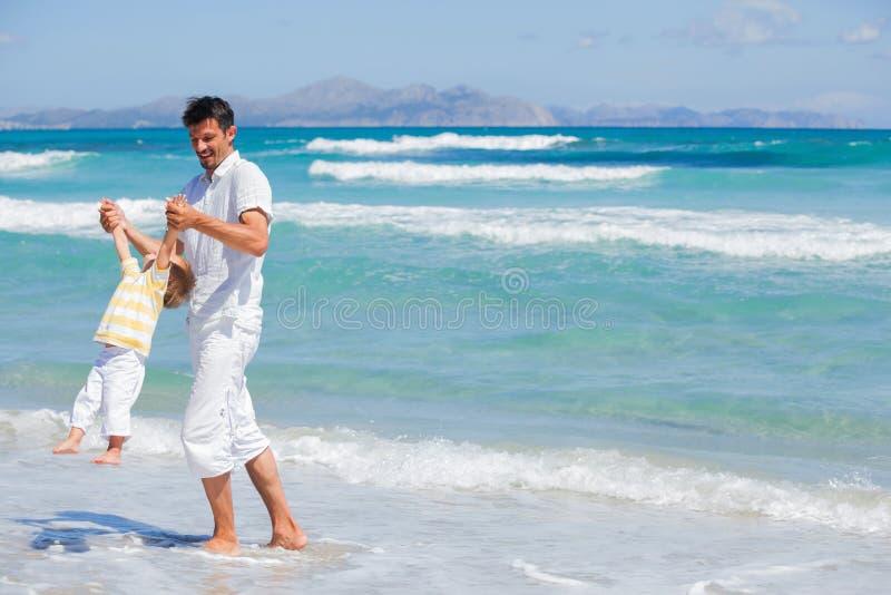 Fader och son som har gyckel på strand fotografering för bildbyråer
