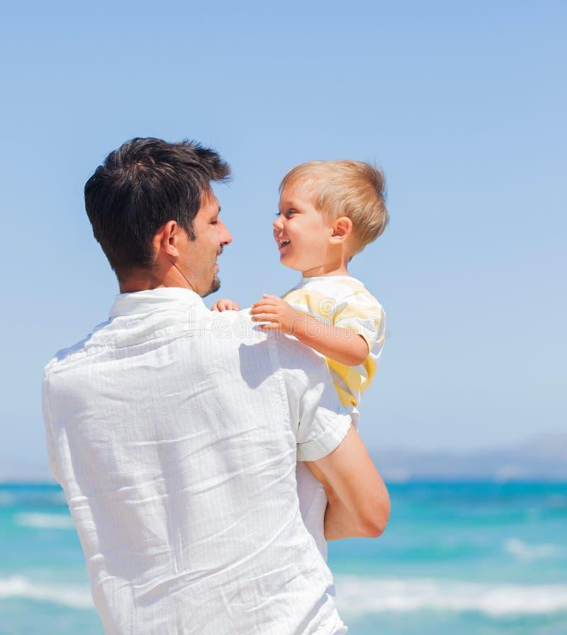 Fader och son som har gyckel på strand royaltyfria bilder