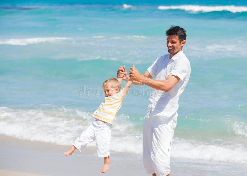 Fader och son som har gyckel på strand royaltyfri foto