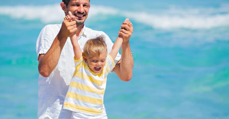 Fader och son som har gyckel på strand arkivbilder