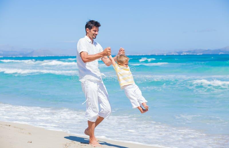 Fader och son som har gyckel på strand arkivfoton