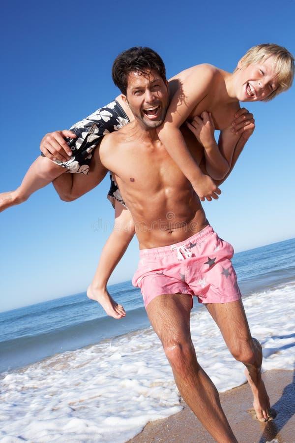 Fader och Son som har gyckel på strand arkivfoto
