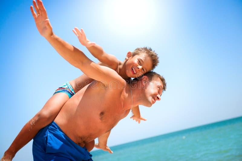 Fader och son som har gyckel på stranden royaltyfria foton
