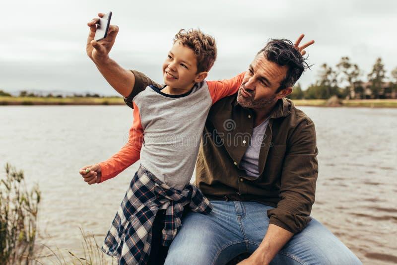Fader och son som har gyckel som utomhus tar selfie royaltyfri fotografi