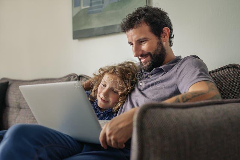 Fader och son som hemma sitter hålla ögonen på en film direktanslutet royaltyfria bilder