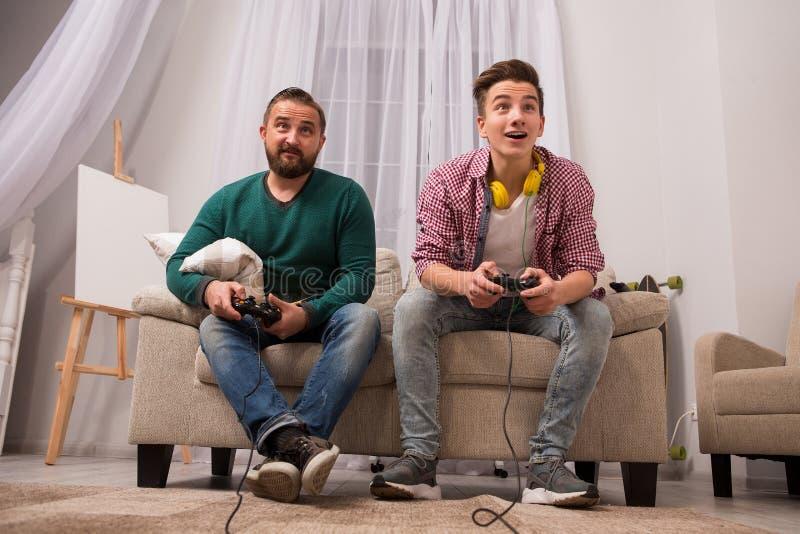 Fader och son som hemma spelar i konsolen royaltyfri fotografi