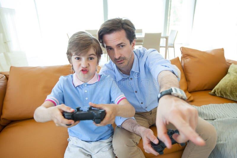 Fader och son som hemma spelar videogamen royaltyfri fotografi