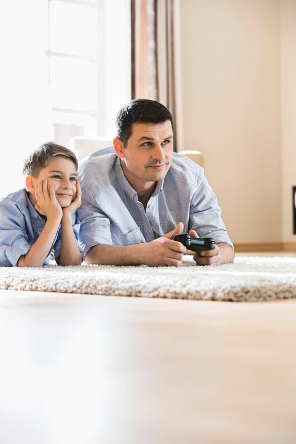 Fader och son som hemma spelar videospelet på golv royaltyfria foton
