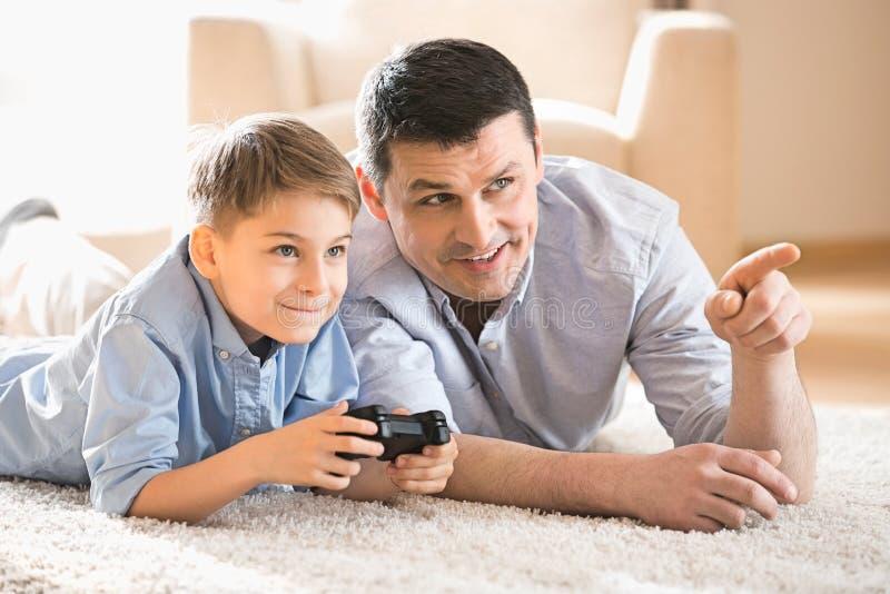Fader och son som hemma spelar videospelet på golv fotografering för bildbyråer