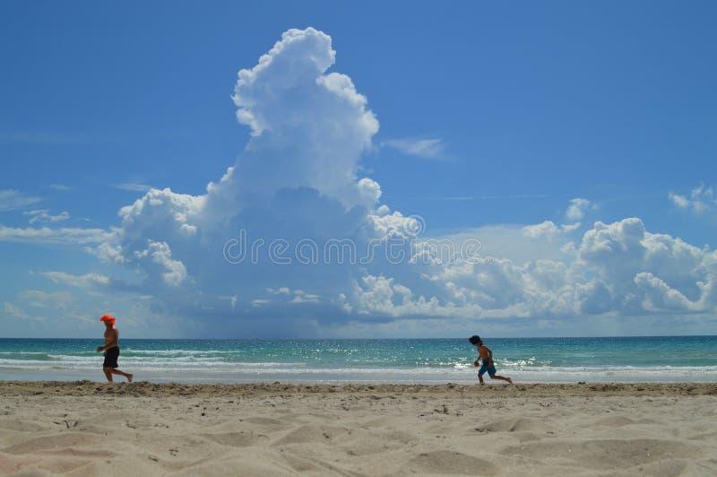 Fader och son som kör längs stranden arkivfoton