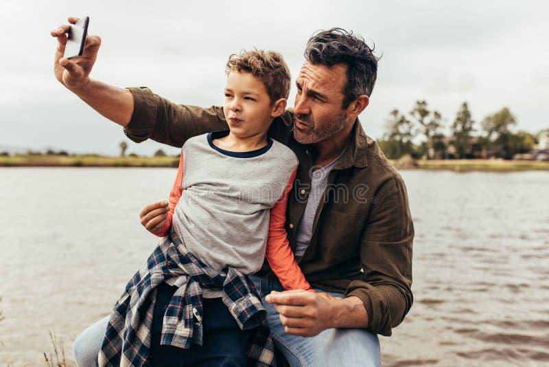 Fader och son som klickar en selfie nära en sjö royaltyfria foton