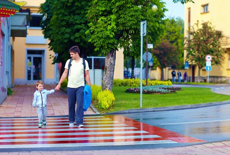 Fader och son som korsar stadsgatan på övergångsställe royaltyfria foton