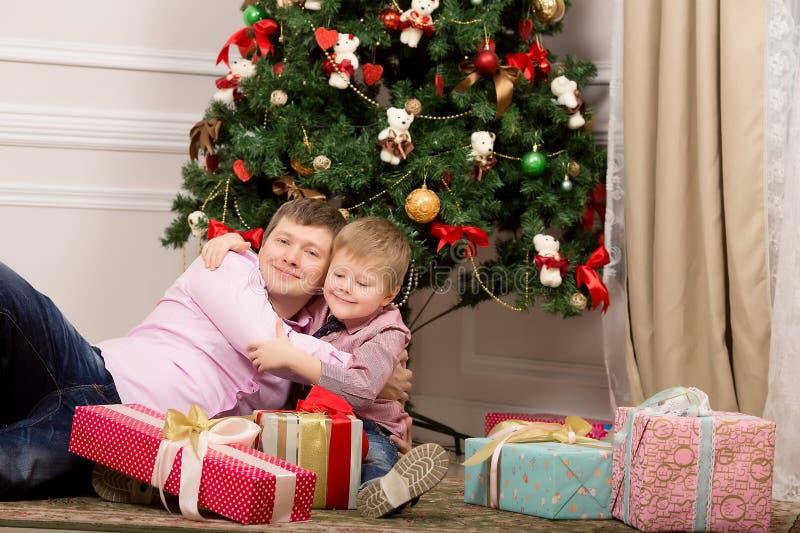 Fader och son som kramar bredvid julgranen nytt år fotografering för bildbyråer