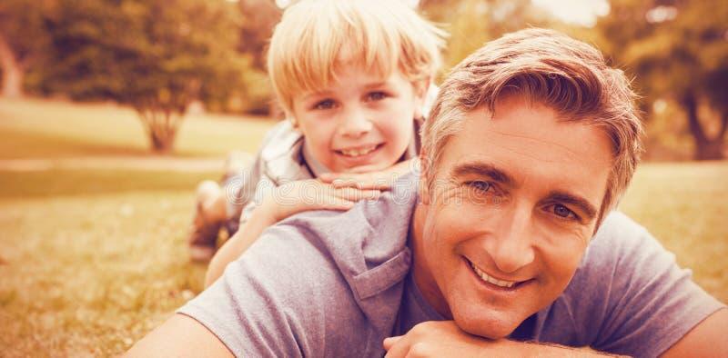 Fader och son som ligger på fält royaltyfri bild