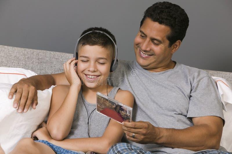 Fader och son som lyssnar till musiksammanträde på säng royaltyfri foto