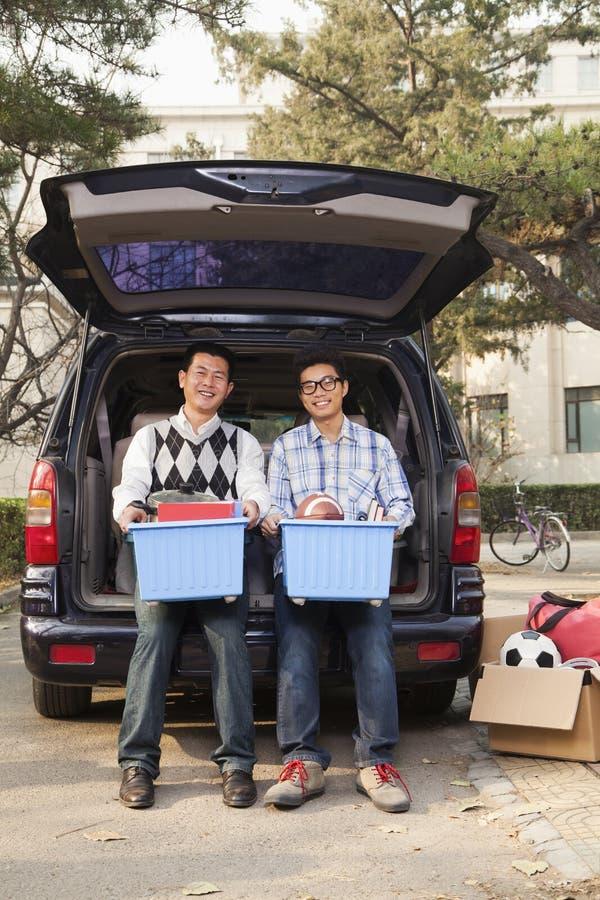 Fader och son som packar upp bilen för högskolan, hållande fack och ser kameran arkivbild