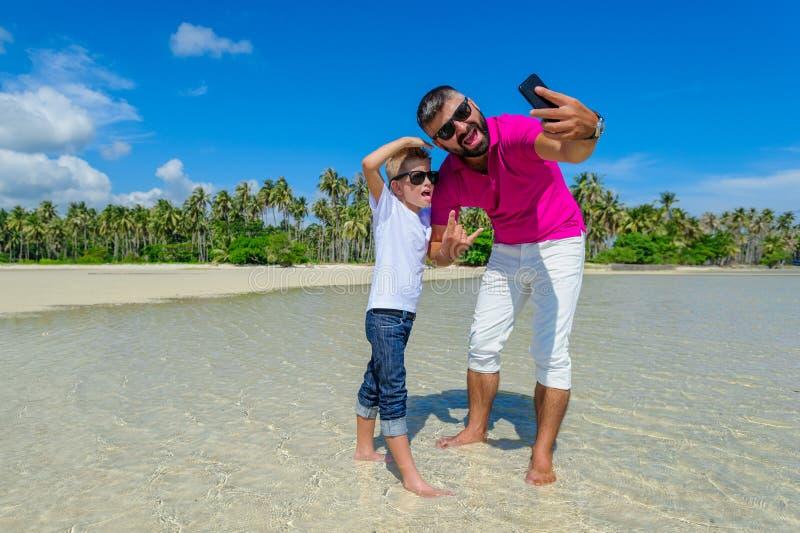 Fader och son som promenerar stranden och att göra selfies och att ha gyckel royaltyfri bild
