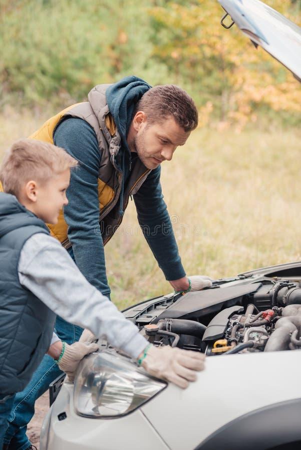 fader och son som reparerar bilen arkivfoton