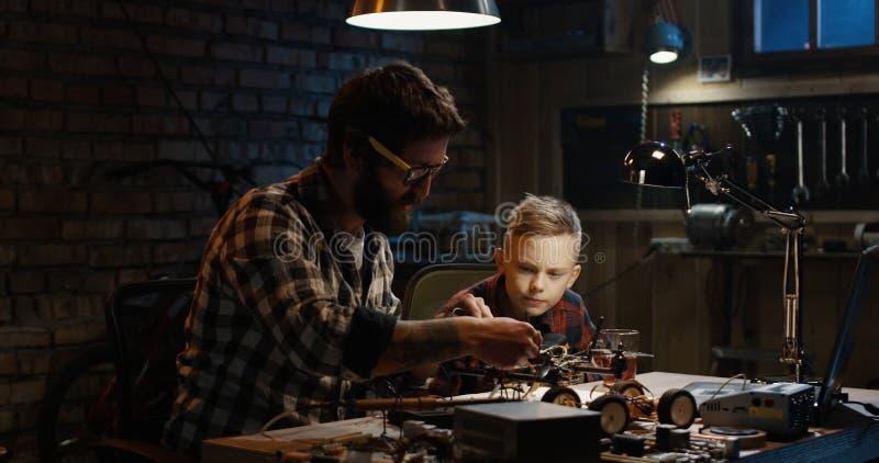 Fader och son som reparerar ett surr arkivfoto