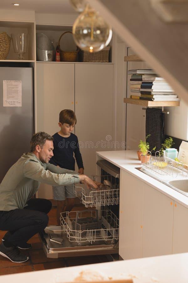 Fader och son som sätter redskap i diskare arkivbild