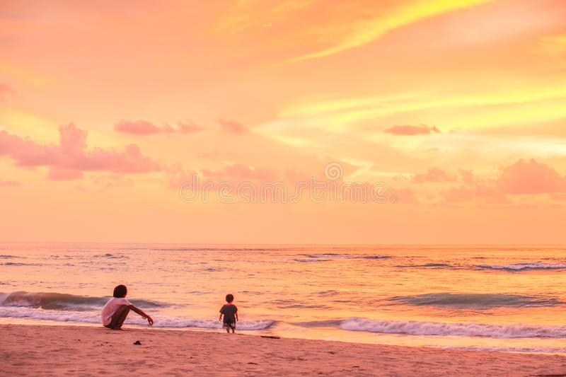 Fader och son som ser solnedgång och fantastisk himmel fotografering för bildbyråer