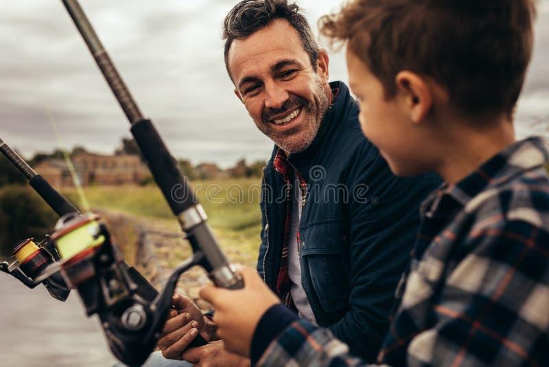 Fader och son som sitter nära ett sjöfiske royaltyfri foto