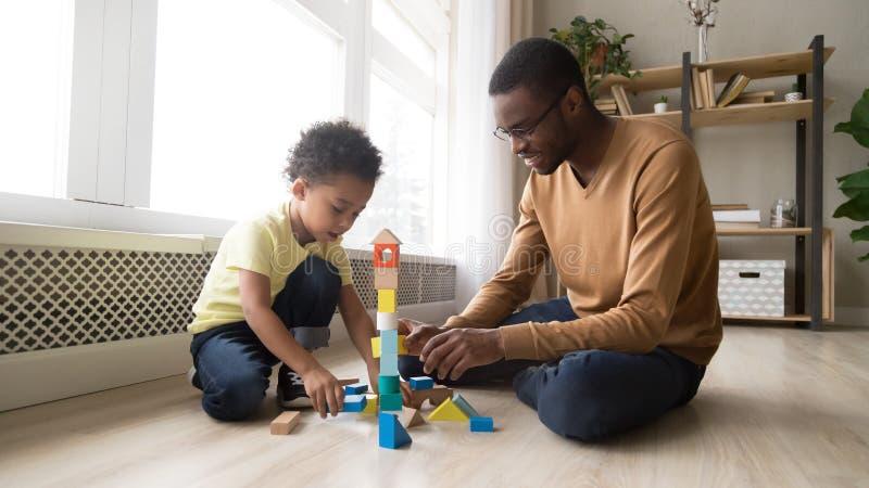 Fader och son som sitter på golvlek med leksakkvarter royaltyfri fotografi