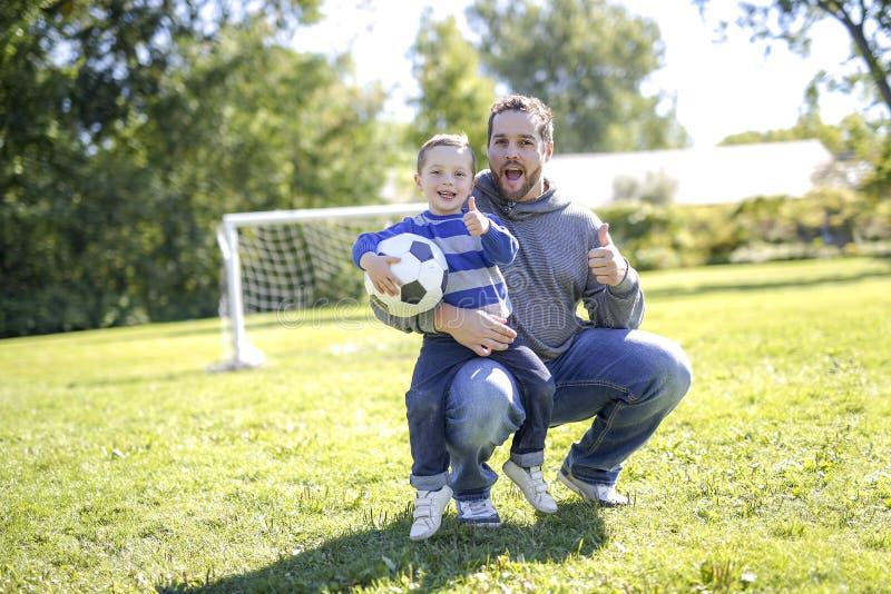 Fader och son som spelar bollen i parkera arkivbilder
