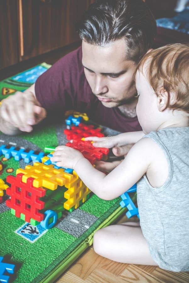 fader och son som spelar den modiga konstruktörn royaltyfri foto