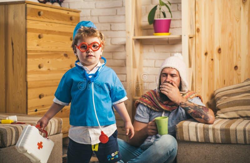Fader och son som spelar doktors-, medicin- och behandlingbegrepp Nöd- medicinsk specialist som besöker tålmodigt hemmastatt arkivfoto