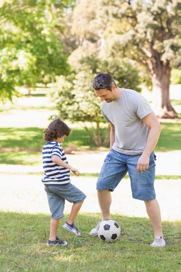 Fader och son som spelar fotboll i parkera arkivbilder