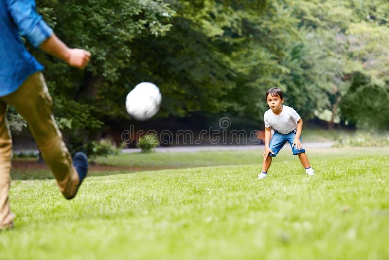 Fader och son som spelar fotboll i parkera arkivfoto