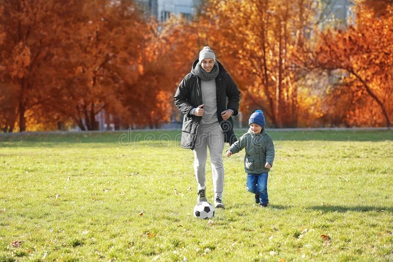 Fader och son som spelar fotboll på graden arkivbilder