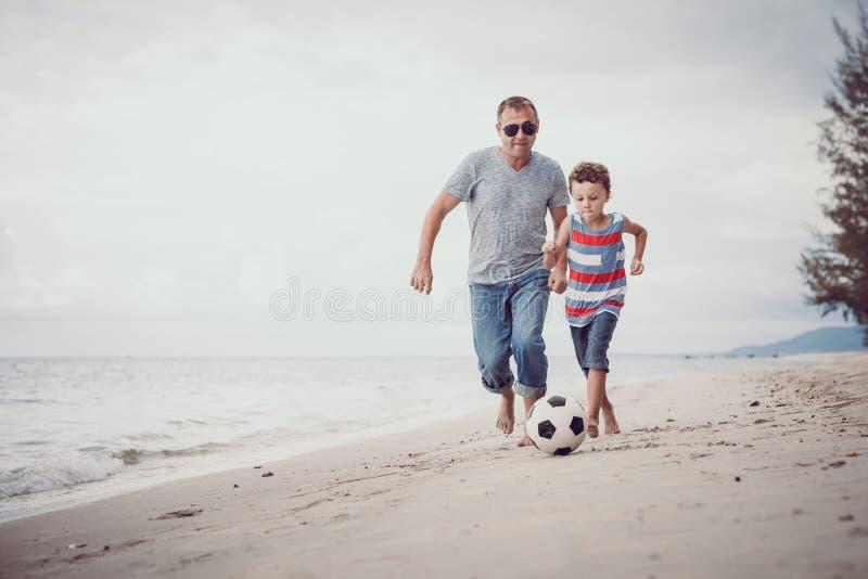 Fader och son som spelar fotboll på stranden på dagtiden arkivbild