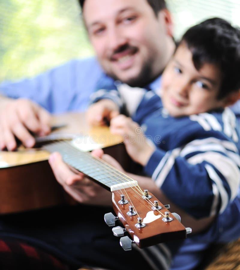 Fader och son som spelar gitarren arkivfoto