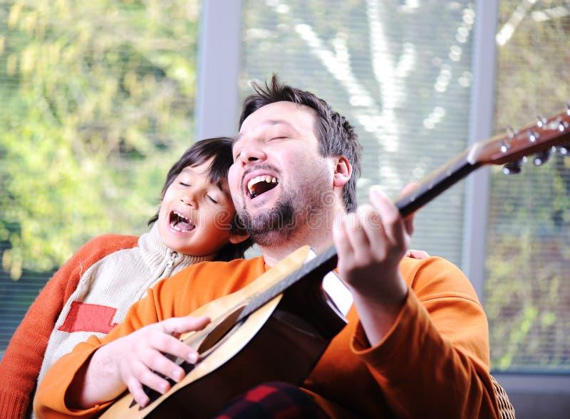 Fader och son som spelar gitarren royaltyfria bilder
