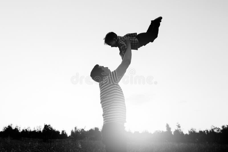 Fader och son som spelar i fält på solnedgångtiden Folk som har gyckel på fältet Begrepp av den vänliga familjen och arkivbild