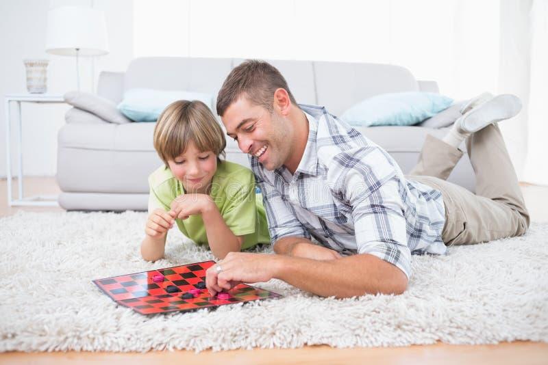 Fader och son som spelar kontrollörleken, medan ligga på päls royaltyfri foto