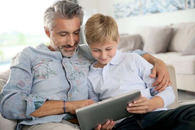 Fader och son som spelar lekar på minnestavlan fotografering för bildbyråer