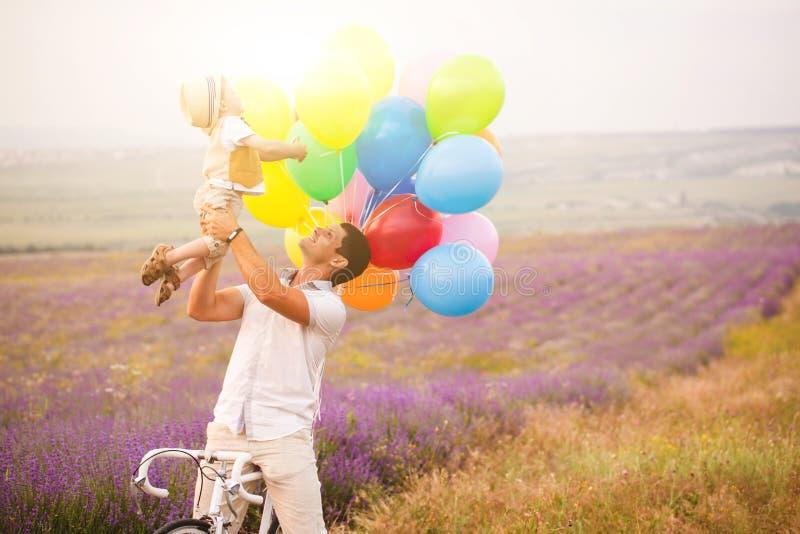 Fader och son som spelar med ballonger på lavendelfält arkivfoto