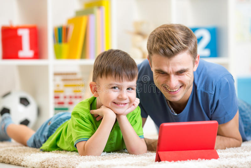 Fader och son som spelar med den digitala minnestavlan arkivfoto