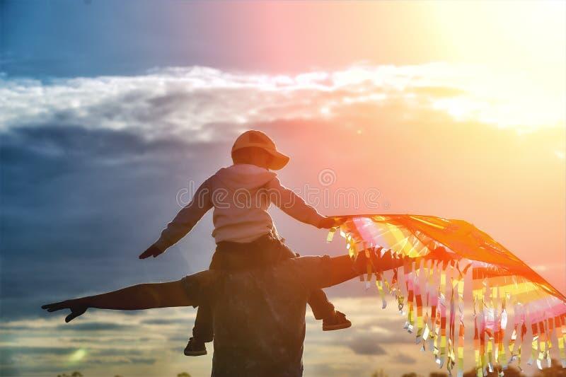 Fader och son som spelar med en drake, i aftonen i fältet royaltyfria foton