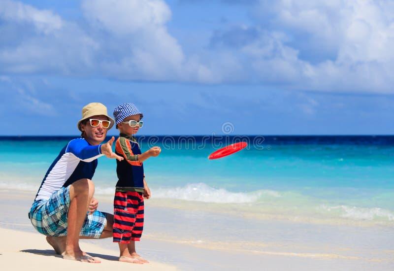 Fader och son som spelar med flygdisketten på stranden royaltyfri bild