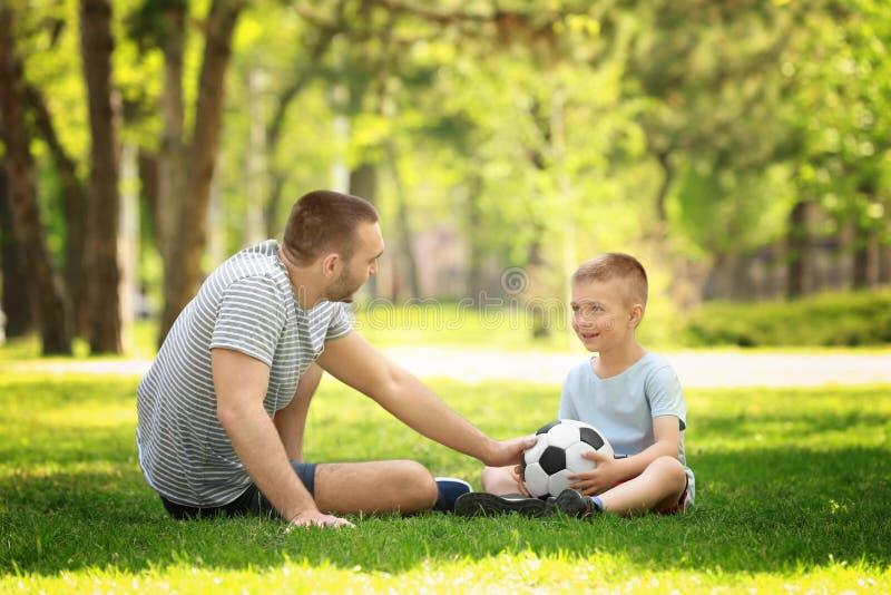 Fader och son som spelar med fotbollbollen på grönt gräs arkivfoto