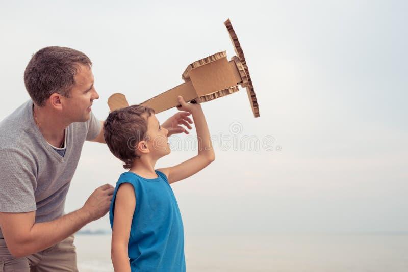Fader och son som spelar med pappleksakflygplanet arkivbilder