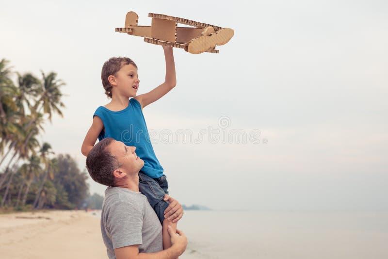 Fader och son som spelar med pappleksakflygplanet royaltyfri fotografi