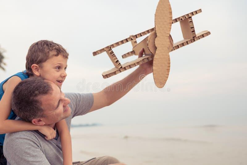 Fader och son som spelar med pappleksakflygplanet royaltyfria bilder