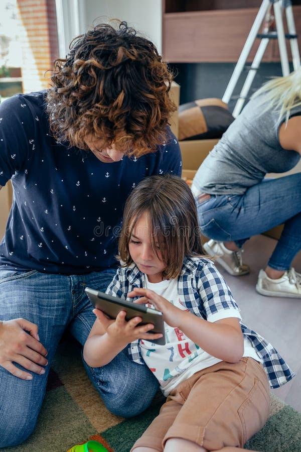 Fader och son som spelar minnestavlan arkivfoto