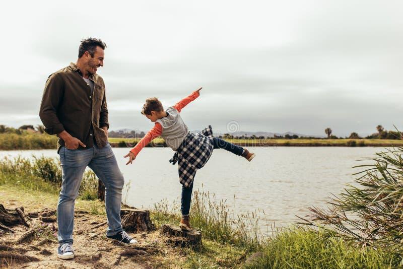 Fader och son som spelar nära sjön royaltyfri bild