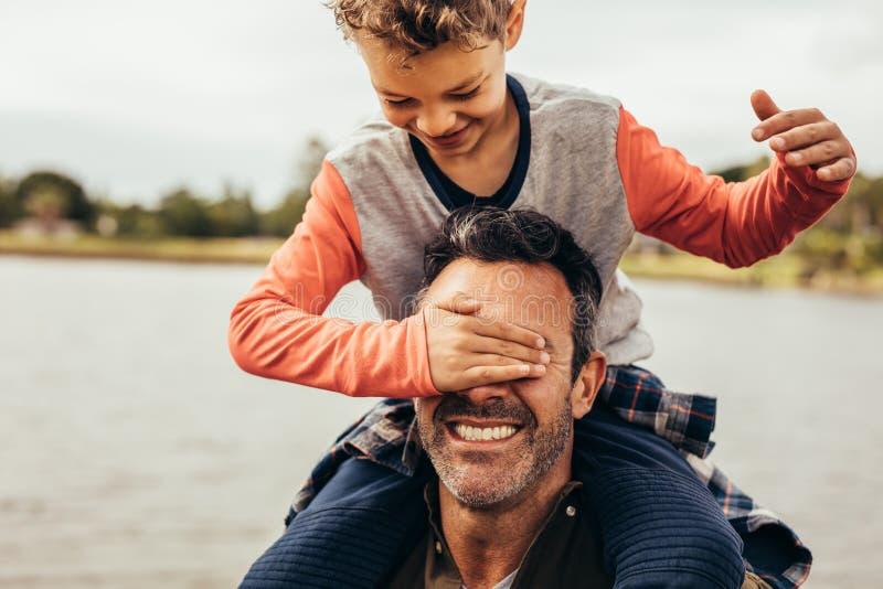 Fader och son som spelar n?ra sj?n royaltyfria foton